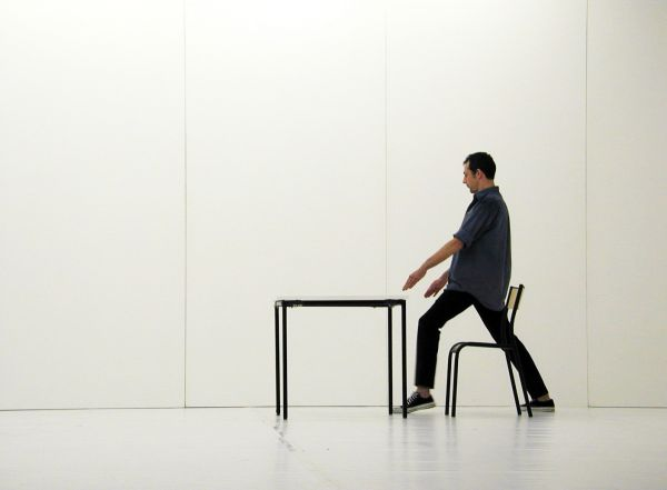 Man at a desk standing up from a chair