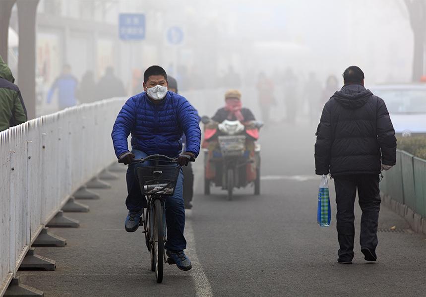 Man cycling bike through Beijing haze